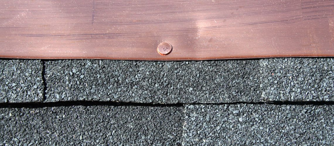 Black asphalt roofing shingles with copper flashing