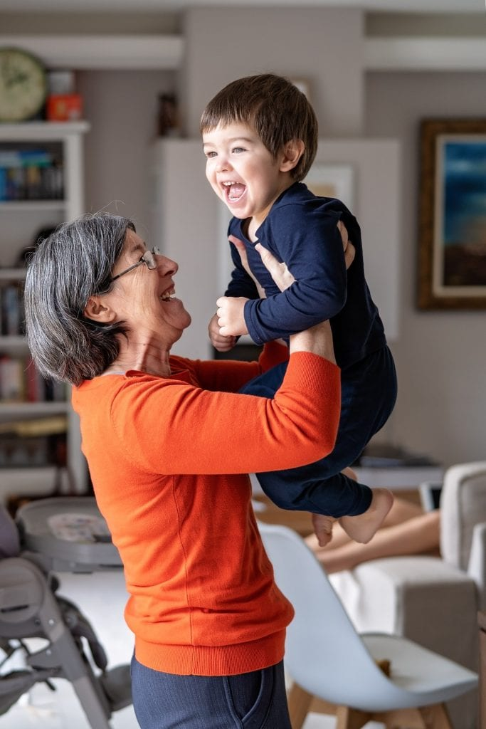 Happy smiling grandmother playing with her little grandson holding him in her arms in the air