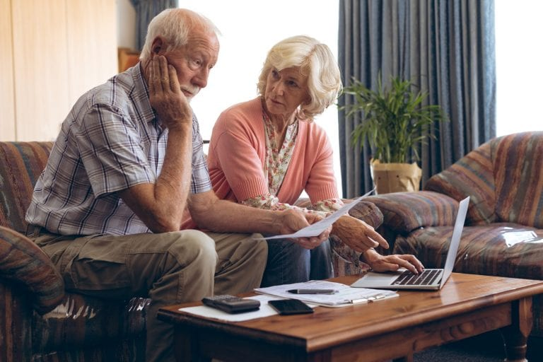 Sad senior couple discussing bill while sitting on vintage sofa at retirement home