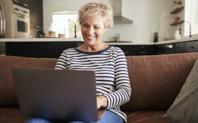 Senior white woman sitting on couch using laptop computer